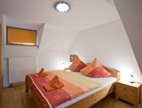 Schlafzimmer mit Schrank und Doppelbett
